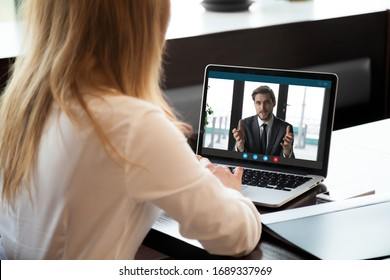 Back view of female employee talk on video call with male colleague or business partner, woman worker communicate online speak on Webcam, have web conference with coworker from home office