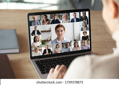 Back view of female employee talk on video call on laptop with diverse colleagues, have group web conference or meeting, woman worker engaged in webcam conversation with coworkers from home - Shutterstock ID 1739378873