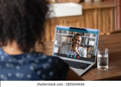 Back view of female employee talk on video call with male colleague or coworker. Woman have webcam conference conversation with husband on laptop at home. Workers engaged in online virtual meeting.
