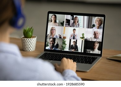 Back view of female employee talk speak on team video call on laptop with diverse businesspeople. Woman engaged in webcam online digital virtual conference or web briefing with colleagues on computer.