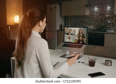 Back view of a female employee working remotely talking to her colleagues about business in a video conference on a desktop computer at home. A multiethnic business team on an online meeting.