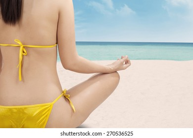 Back view of female model doing meditation while sitting at the beach