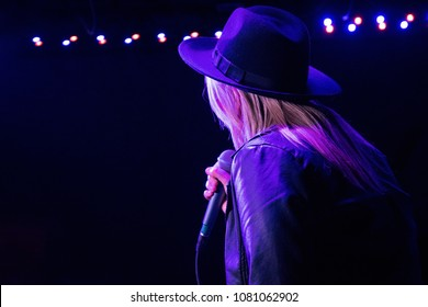 Back view of a female singer on the stage. Dark background, concert spotlights.