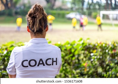 Back view of a female soccer, football, coach in white coach shirt watching her team play at an outdoor football field