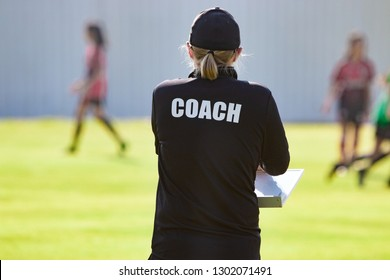 Back view of female sport coach in black COACH shirt at an outdoor sport field, watching her girl football team