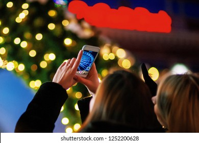 Back view of female tourist making image of Santa Monica pier lights at night on cellphone sightseeing on weekends, hipster girl shooting video of shining ferris wheel via telephone in amusement park