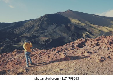 back view female tourist taking picture of summit Etna Volcano with mobile phone, Sicily