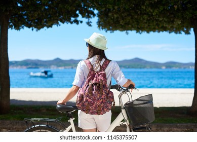 Back view female tourist in white closing, sunhat and backpack standing with bicycle on sidewalk near coast under trees and mountains view on opposite shore background. Tourism and vacations concept.