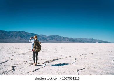 Back view of female traveler using mobile camera for taking picture of dry landscape exploring death valley,woman photographer having adventure in trip of lowest american point making image on phone