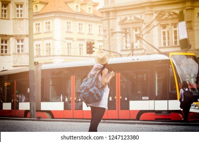 Back view of Female traveler waiting the tram,using public transportation in foreign country.Tourist in Prague ,Czech