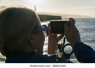 Back view of female young girl photographing landscape on mobile phone