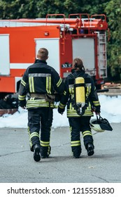 back view of firefighters in fireproof uniform walking on street with fire truck behind