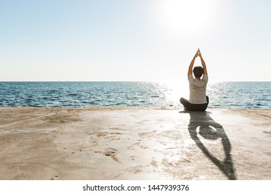 Back view of a fit asian man doing yoga exercises at the beach, meditating