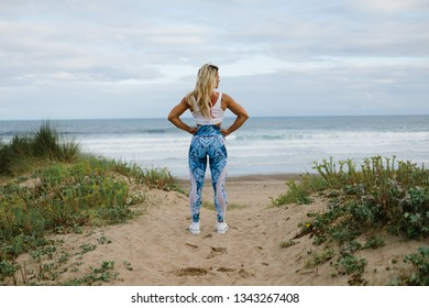 Back view of fit muscular sporty young woman on summer morning outdoor fitness workout at the beach.