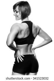 Back view of fit smiling female athlete against of white background. Isolated, studio shot