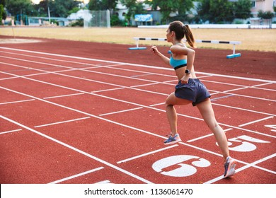 Back view of a fit sportswoman running a distance at the stadium