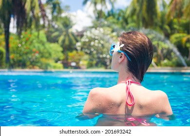 back view of fit woman with flower in hair in luxury spa pool