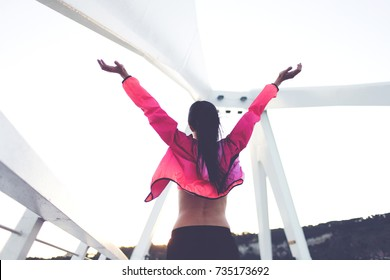 Back view of fit woman with slender body standing with raised hands felling freedom while rest after workout, young happy female enjoying good evening and weather after training in the fresh air
