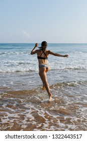Back view of fit young woman in bikini running into de sea at the beach. Outdoor fitness, healthy lifestyle and summer freedom concept.