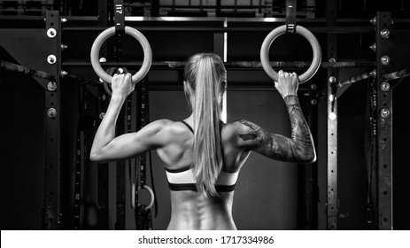Back view of fit young woman with ponytail in sports wear Healthy woman exercising with gymnastic rings Female bodybuilder with power hand, triceps, arms, rear in gym Black and white horizontal photo.