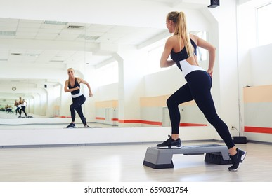 Back view of fitness instructor making step aerobics in gym. Sporty woman training step aerobics in gym