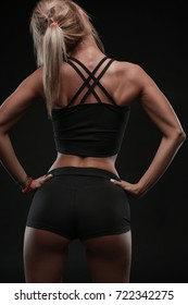 Back view of fitness trainer, strong back, muscular shoulders, strong arms, tanned, distinctive backbone, slim waist, hans on hips, black shorts and top, perfect slim sporty body on black background