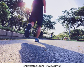 Back view of fitness young man runner fast running on the road in green City park against sunrise morning.