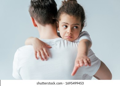 back view of foster father taking away sad african american daughter isolated on white, custody concept