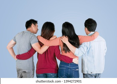 Back view of four best friends embracing each other while standing in the studio