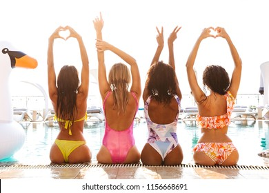 Back view of four happy young women in swimwear sitting together, having fun at the pool outdoors, arms raised