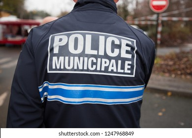 back view of french policeman police municipal means local police in french