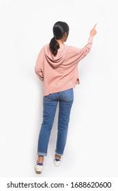 Rückansicht Volllange junge Frau in braunem Pullover mit blauer Jeans junge Frau in braunen Hemden mit weißen Jeans einzeln mit Händen und Fingern auf der Seite