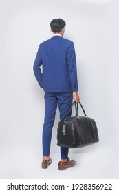 Rückansicht mit vollständiger Länge und jugendlicher Mann mit blauem Anzug, Krawatte mit weißem Hemd und blauer Hose, braune Schuhe mit Handtasche auf weißem Hintergrund,