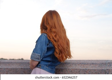 Back view of Ginger haired girl in blue jeans jacket looking at view, outdoor image in front of sunset sky. Ginger hair