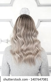 Back view of girl with beautiful blond sombre hairstyle standing in hair salon, Balayage technique concept