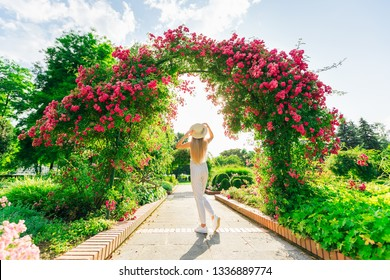 back view of a girl with boater near the arches with pink roses. park