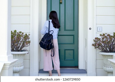 back view of girl college student carrying backpack back to home using key opening door. young office lady from work unlock house to enter the room. two plants beside front door in white wooden house