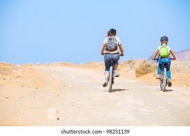 Back view of girl with her mother having a weekend excursion on their bikes on a summer day in beautiful landscape