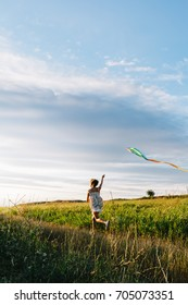 Back view of girl holding kite and running in field under sky with overcast.