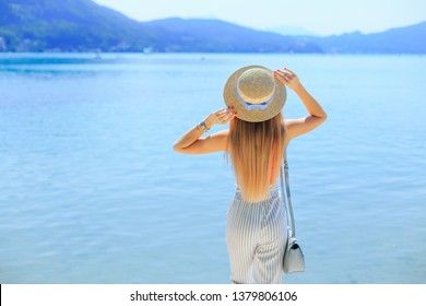 back view for a girl with long hair she holds her arms on the boater. Mountain lake.