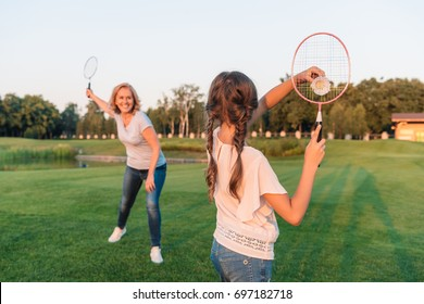 back view of girl playing badminton with grandmother on green lawn