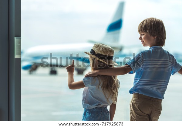 back view of girl pointing away while looking out window together with brother in airport