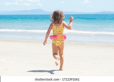 Back view of girl running in swimsuit on the beach towards the blue sea on beautiful sunny day. The child runs on the beach. Happy carefree girl wearing swimsuit having fun on summer vacation.