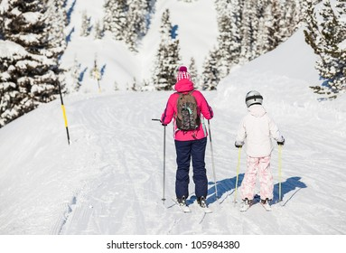 Back view of girl in ski goggles and a helmet with his mother, Zellertal, Austria. Vertical view
