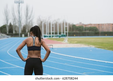 Back view of girl stretching neck while standing on sports ground.