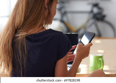 Back view of girl in t-shirt chatting over cell phone sitting at table with green cup and laptop in sunlight.