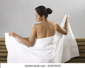 Back view of a girl wrapping her half naked body