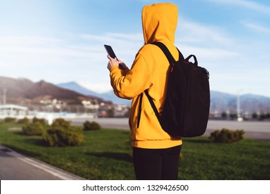 Back view. Girl in yellow hoodie with backpack uses smartphone, writes text message. Woman traveler checks email during adventure trip.Tourist uses app for travelers on mobile. In background mountains