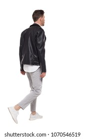 Back view of going  handsome man in a leather jacket and trousers. walking young guy . Rear view people collection.    Isolated over white background. Brunette with a stylish hairstyle leaves