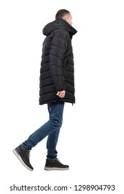 Back view of going  handsome man in jeans and winter jacket.  walking young guy . backside view of person.  Isolated over white background. The guy in the long jacket is slowly going sideways.